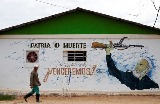 "A man passes by an image of Cuba's former President Fidel Castro with a writing that reads ""Motherland or Death"", Bauta"